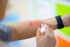 Los lápices labiales pintan en el brazo para la prueba colorido imagenes de archivo
