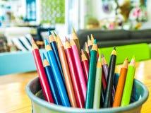 Los lápices multicolores se combinan en una caja de acero en un escritorio en th foto de archivo libre de regalías