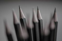 Los lápices negros inclinan el primer con empañado más en el backround Foto de archivo libre de regalías