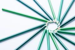 Los lápices verdes arreglaron en un círculo en lado derecho del thr en el fondo ligero, visión superior Foto de archivo