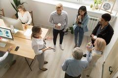 Los líderes de equipo encuentran a internos multirraciales en la oficina coworking, v superior imágenes de archivo libres de regalías