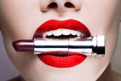 Los labios de las mujeres hermosas, maquillaje elegante brillante barra de labios en los dientes, concepto del palillo de la moda foto de archivo libre de regalías