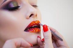 Los labios rojos cubiertos con los diamantes artificiales, artista de maquillaje tratan diamantes artificiales en modelos del lab fotografía de archivo libre de regalías