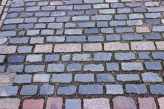 los ladrillos Multi-hued componen un modelo variado donde muchos pies han pisado Foto de archivo libre de regalías