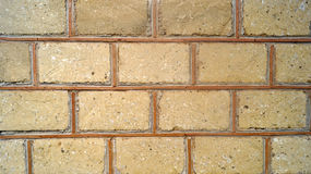 Los ladrillos simulados del color de la arena divididos por la pared de las rayas del ocre texturizan el fondo Imagenes de archivo