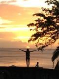Los levés de los sujetadores de une ombre de personne del avec de Coucher de soleil levantan el campañol del je Foto de archivo