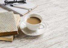 Los libros, abren una libreta en blanco y una taza de té con leche Fotos de archivo