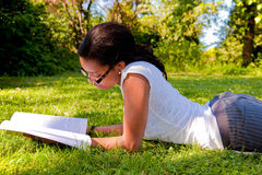 Los libros de lectura jovenes del estudiante en la escuela estacionan Fotografía de archivo libre de regalías