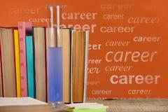 Los libros en la tabla contra la pizarra anaranjada con carrera mandan un SMS Imagen de archivo
