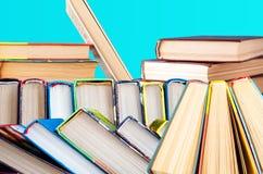 Los libros en un fondo azul apilaron doblado, endecha con una cuesta fotos de archivo