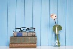 Los libros llenan, los vidrios y rosa del blanco en la botella Imagenes de archivo
