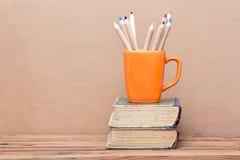 Los libros se elevan y taza anaranjada con los lápices coloreados Fotos de archivo libres de regalías