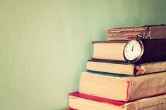 Los libros viejos con el vintage embolsan el reloj en una tabla de madera imagen filtrada retra Foto de archivo