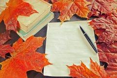 Los libros viejos con la hoja amarilleada y la pluma vieja de la tinta cerca del otoño todavía secan las hojas de arce - vida del Foto de archivo