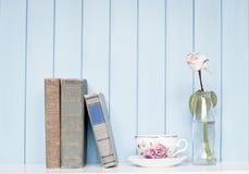 Los libros viejos, la taza de China y subieron en la botella en el estante Imagen de archivo libre de regalías