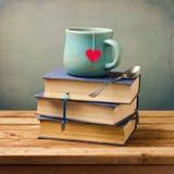Los libros y la taza viejos del vintage con el corazón forman imagen de archivo libre de regalías