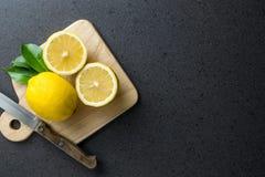Los limones están encima de la tabla de cortar de madera con el cuchillo foto de archivo