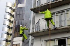 Los limpiadores de ventana trabajan en el alto edificio de la subida Imagen de archivo libre de regalías