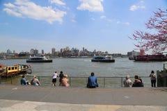 Los locals de los turistas y de Nueva York disfrutan igualmente de un día soleado en el puerto del sur de la calle, Lower Manhatt foto de archivo