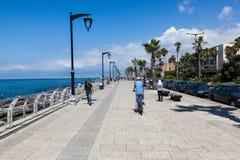 Los locals no identificados caminan a lo largo de la playa alrededor del muelle en Beirut Imágenes de archivo libres de regalías
