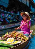 Los locals tailandeses venden la comida y recuerdos en el mercado flotante famoso de Damnoen Saduak, Tailandia Foto de archivo libre de regalías