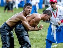 Los luchadores adolescentes luchan para la supremacía durante la competencia en el festival de lucha del aceite turco de Kirkpina Foto de archivo