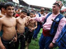 Los luchadores jovenes saludan a un músico gitano en el festival de lucha del aceite turco de Kirkpinar en Edirne en Turquía Foto de archivo