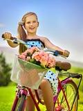Los lunares blancos que llevan de la muchacha del niño visten paseos montan en bicicleta en parque Fotos de archivo