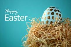 Los lunares del oro en trullo azul adornaron el huevo de Pascua en fondo azulverde sólido del color en colores pastel Imagen de archivo libre de regalías