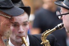Los músicos acercan a un espectador en la calle Foto de archivo libre de regalías