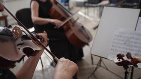 Los músicos irreconocibles de la orquesta sinfónica juegan en los instrumentos musicales de madera cerca se colocan con las notas almacen de metraje de vídeo