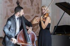 Los músicos juegan el violín y el contrabajo imagen de archivo