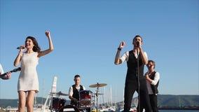 Los músicos modernos realizan una canción cerca del mar en un partido corporativo en el d3ia almacen de metraje de vídeo