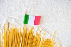 Los macarrones crudos de los espaguetis de las pastas y la pequeña bandera italiana en blanco floured el fondo Imagen de archivo