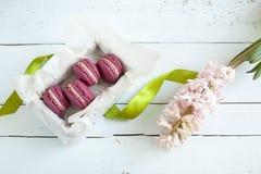Los macarrones franceses carmesís dulces con la caja y el jacinto en luz teñieron el fondo de madera Imagen de archivo libre de regalías