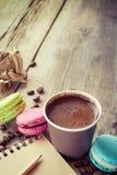 Los macarrones, la taza de café del café express y el bosquejo reservan en rústico de madera Imagenes de archivo