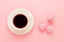 Los macarrones rosados hechos en casa y una taza de café en fondo rosado entonaron, visión superior Fotografía de archivo