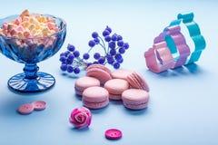Los macarrones rosados se apelmazan con las melcochas mullidas coloridas en florero azul imágenes de archivo libres de regalías