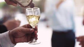 Los man's dan el vino blanco de colada en una copa Banquete de boda, boda italiana Ciérrese encima de la visión, cámara lenta o almacen de metraje de vídeo