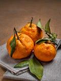 Los mandarines grandes anaranjados se colocan en una servilleta de lino Fotografía de archivo