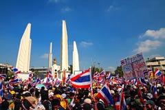 Los manifestantes aumentan banderas y la bandera tailandesas en el monumento de la democracia Fotos de archivo