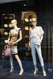 Los maniquíes que se colocan en la exhibición de la ventana de tienda de la ropa informal para mujer hacen compras fotos de archivo