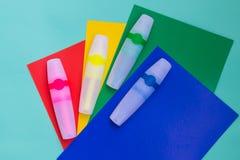 Los marcadores o la pluma coloreados brillantes del fieltro están situados en las hojas del colo Foto de archivo libre de regalías