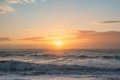 Los mares agitados anaranjados azules de la puesta del sol del océano agitan amanecer de la oscuridad Fotografía de archivo