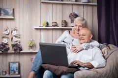 Los mayores felices juntan la lectura del ordenador portátil en sitio acogedor; fotos de archivo libres de regalías