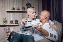 Los mayores juntan sentarse en silla, abrazan y beben el café; Foto de archivo libre de regalías
