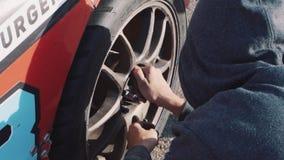 Los mecánicos cambian la rueda en un coche de competición metrajes