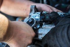 Los mecánicos con las manos sucias reparan el arrancador quebrado en el coche Automot fotos de archivo libres de regalías