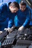 Los mecánicos concentrados que trabajan en el coche explotan Foto de archivo