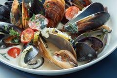 Los mejillones cocieron al vapor apenas para comer en un plato azul Imagen de archivo libre de regalías